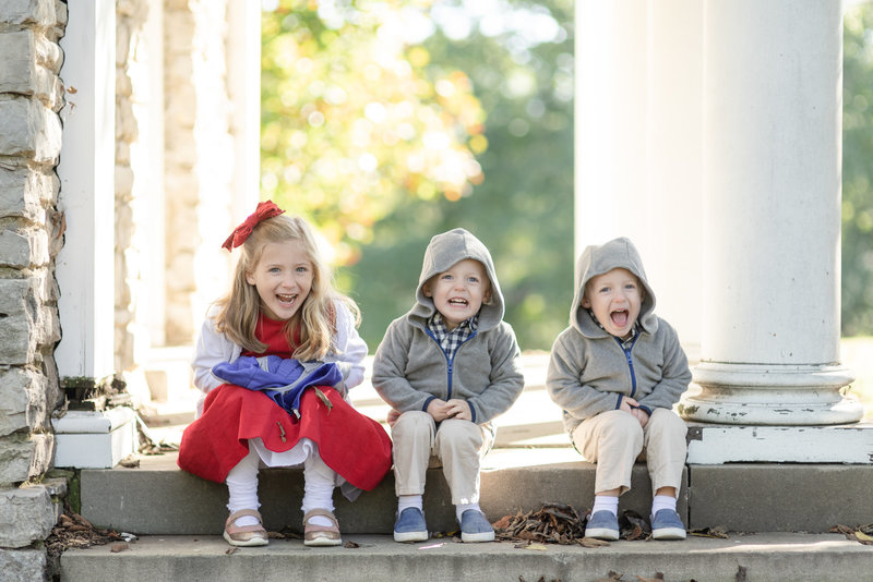 Three siblings are sitting together on a step in a park in Nashville Tennessee on a very cold morning but are laughing at the camera