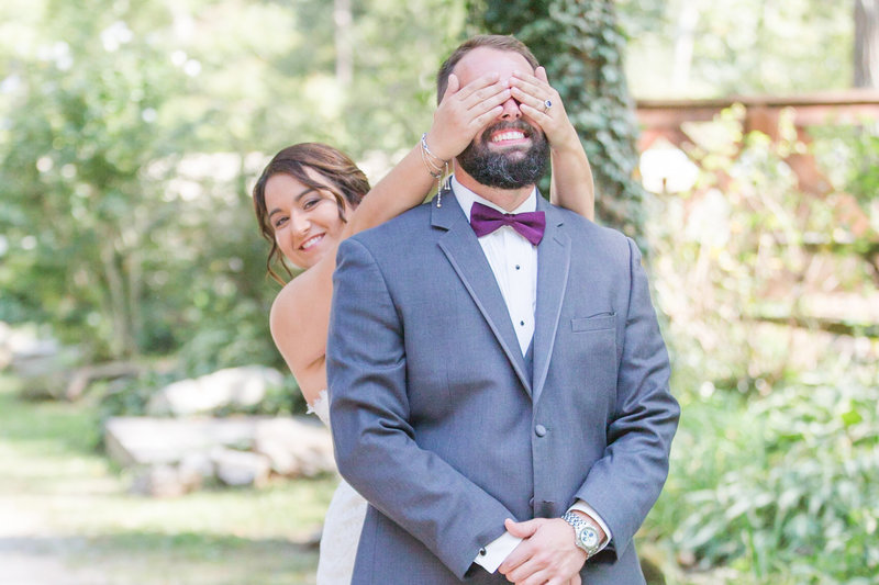 Bride smiles while covering her groom's eyes from behind on their wedding day