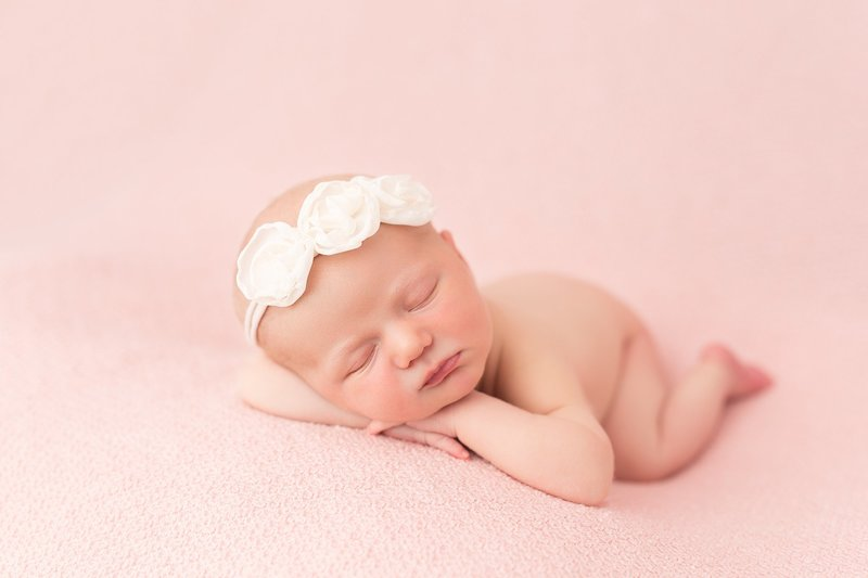 baby girl posed on pink blanket with white headband
