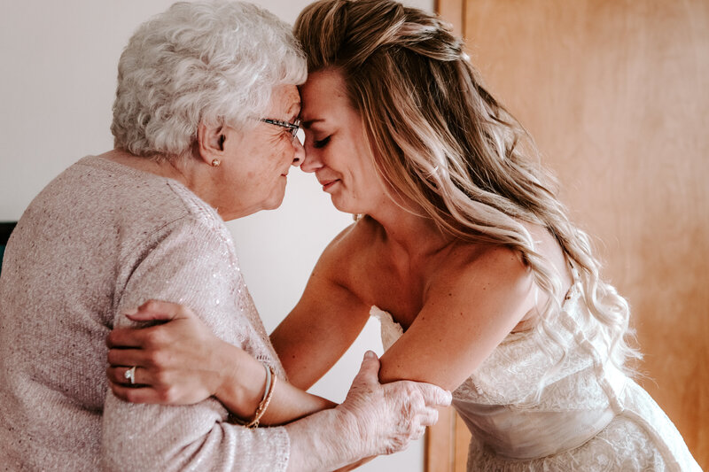 bride touching her forehead to grandmother's