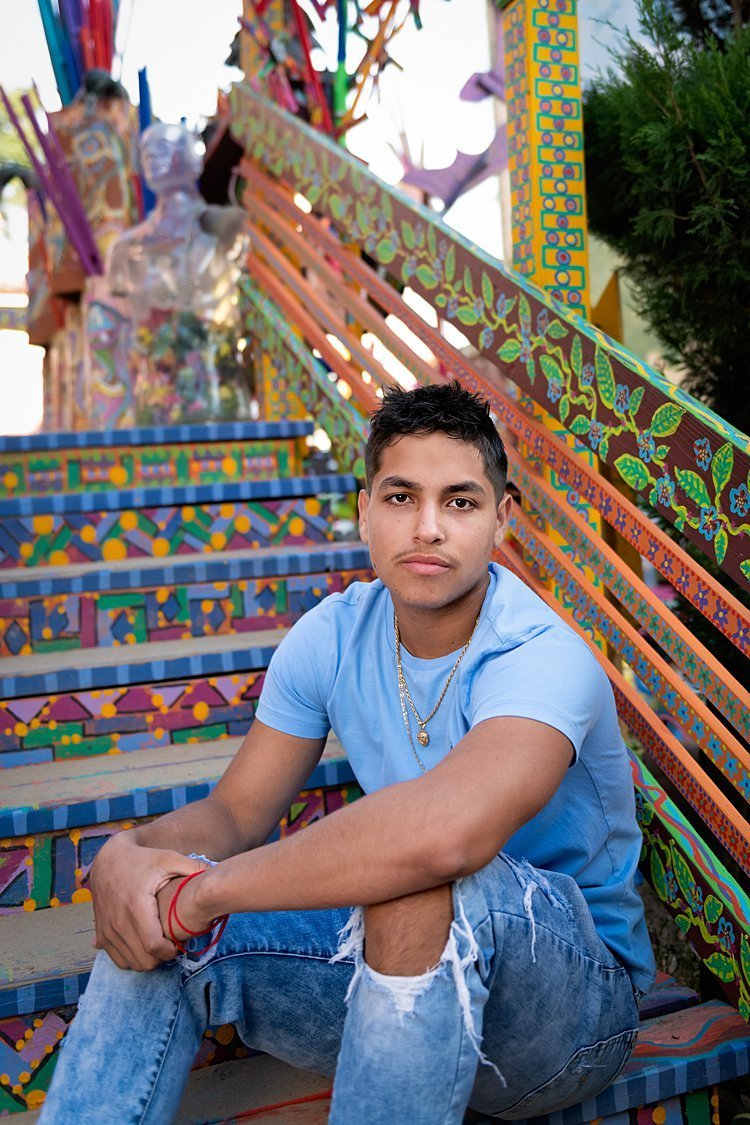 High school senior boy in light blue polo tee seated on colorful painted steps at Randyland in Pittsburgh, PA