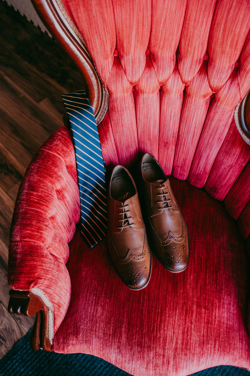 A man's dress shoes and tie sit on a red velvet chair