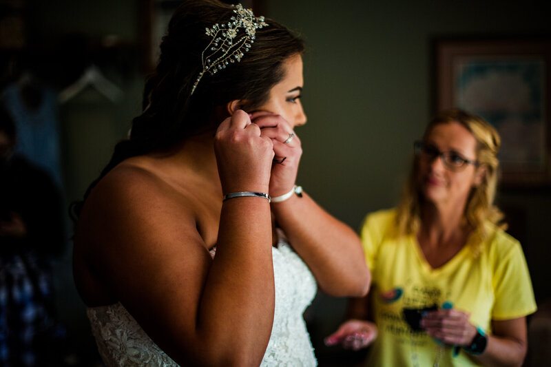 Bride puts in earrings while getting ready for Port Farms weding