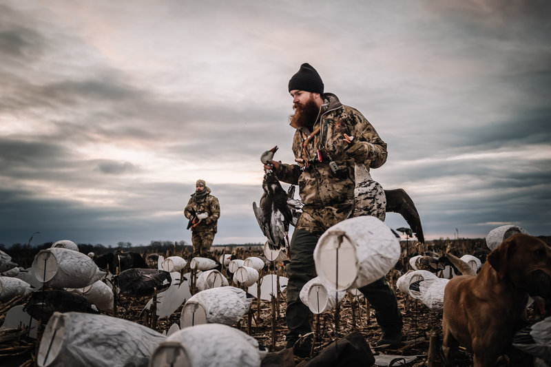 Chase White hands full of geese in Kansas