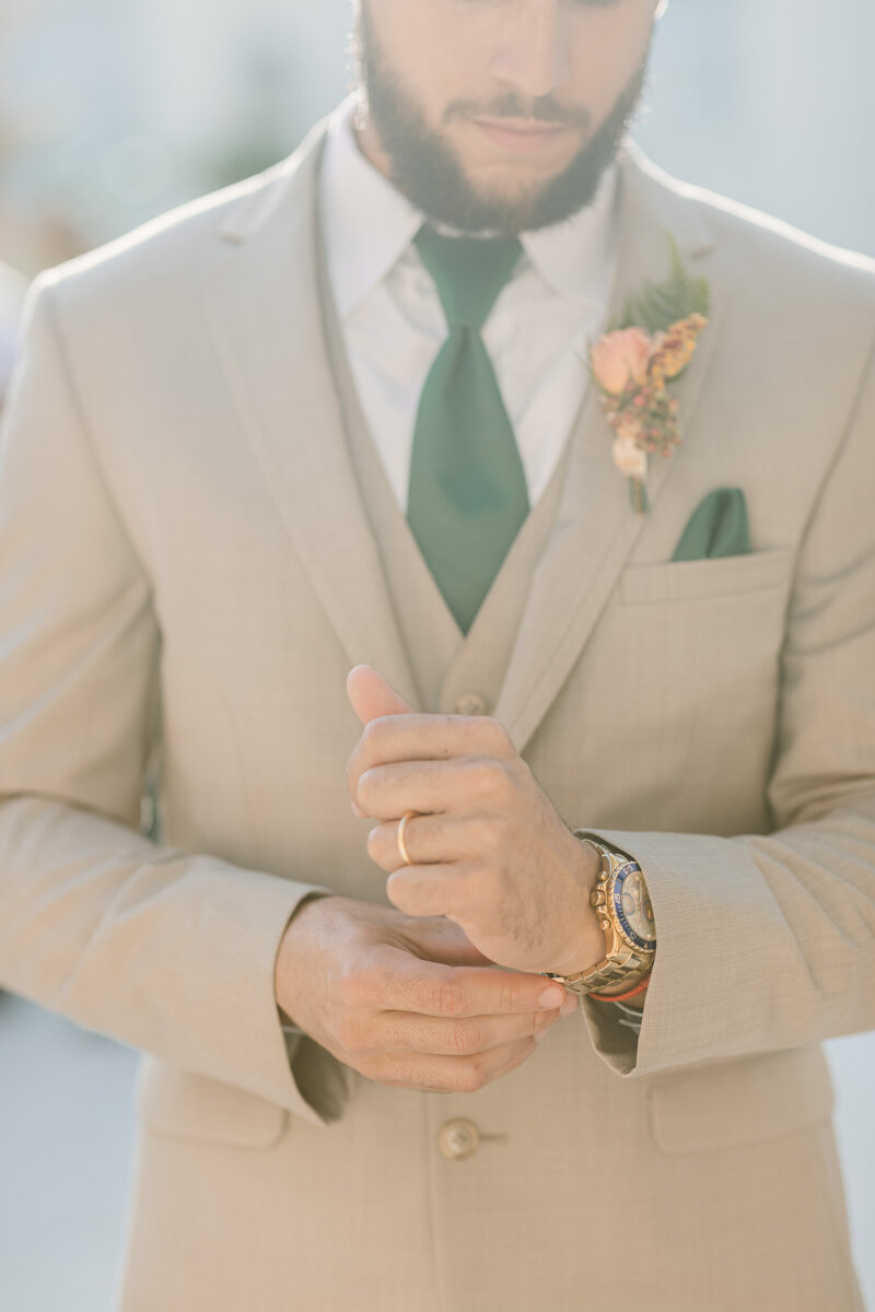 Groom adjusts the cuff of his wedding suit
