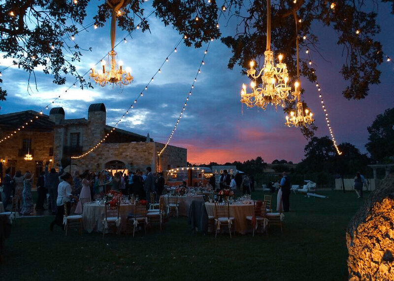 A wedding reception is set on a the grass with chandeliers hanging from the trees with the villa beyond.