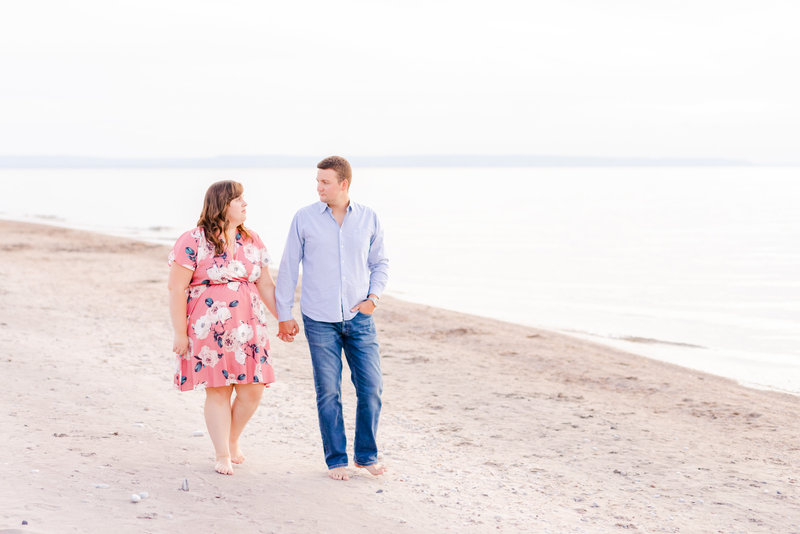Engaged couple walking hand in hand down a beach.
