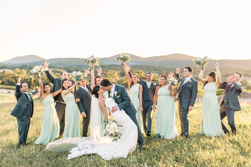 Wedding party cheering as the bride in groom kiss with mountains in the background.