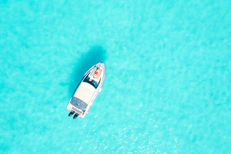 Drone Aerial view woman swimwear on her boat in the blue lagoon of Bora Bora