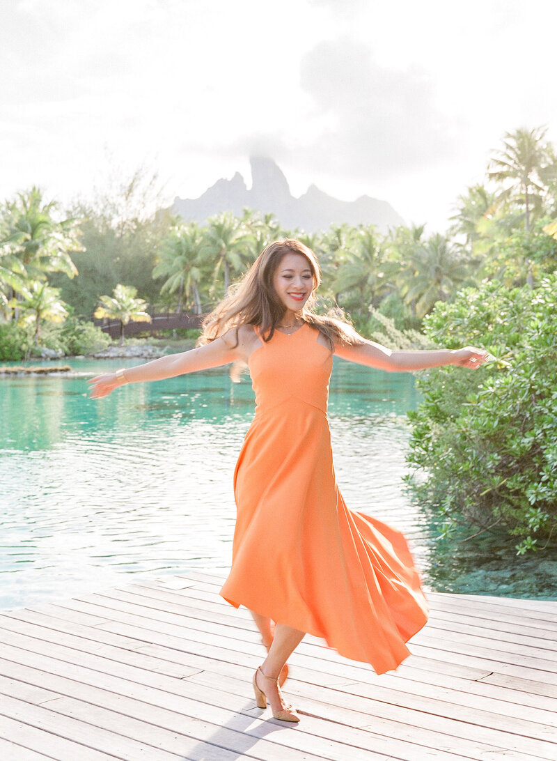 Woman dancing with orange dress in the St Regis Bora Bora