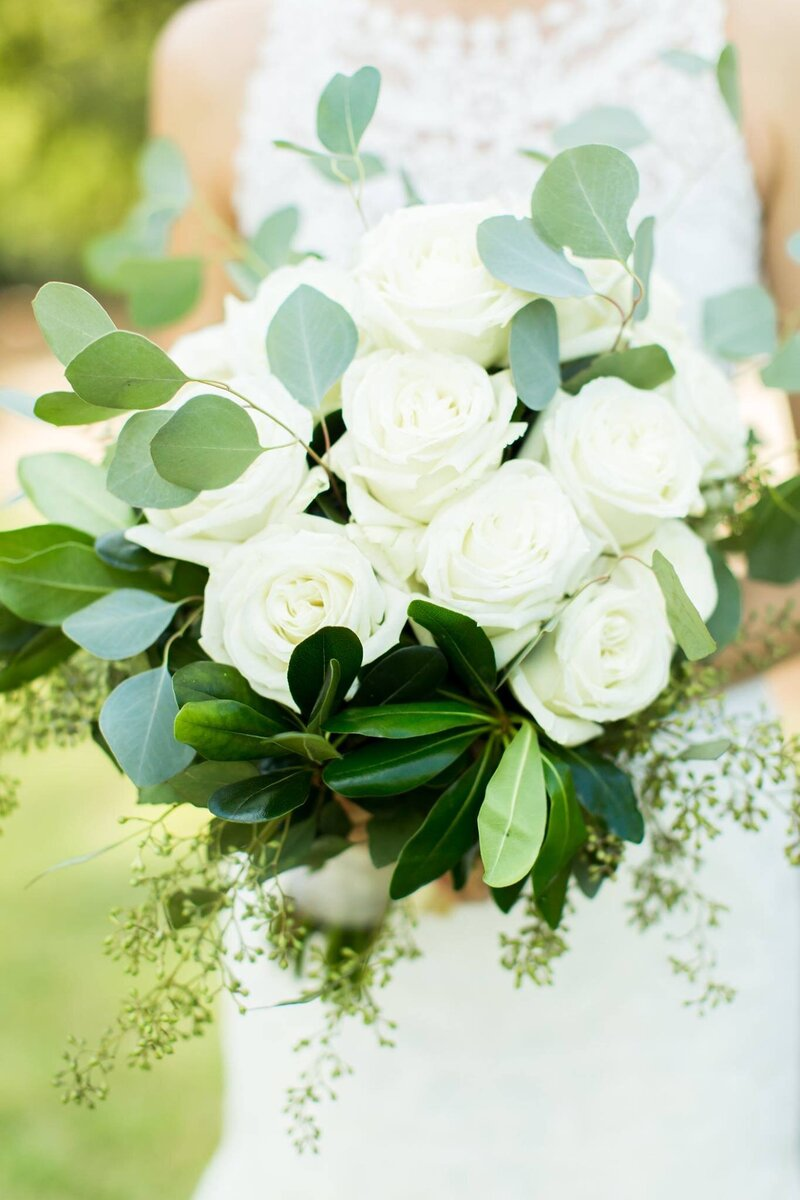 white roses and eucalyptus with seeds in a bridal bouquet