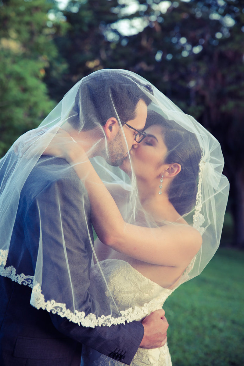 Bride and Groom kiss while wrapped under veil.