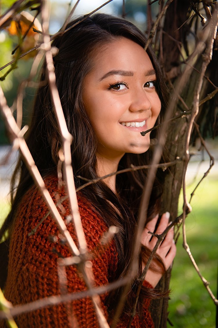 Close-up of high school senior girl among woody vines