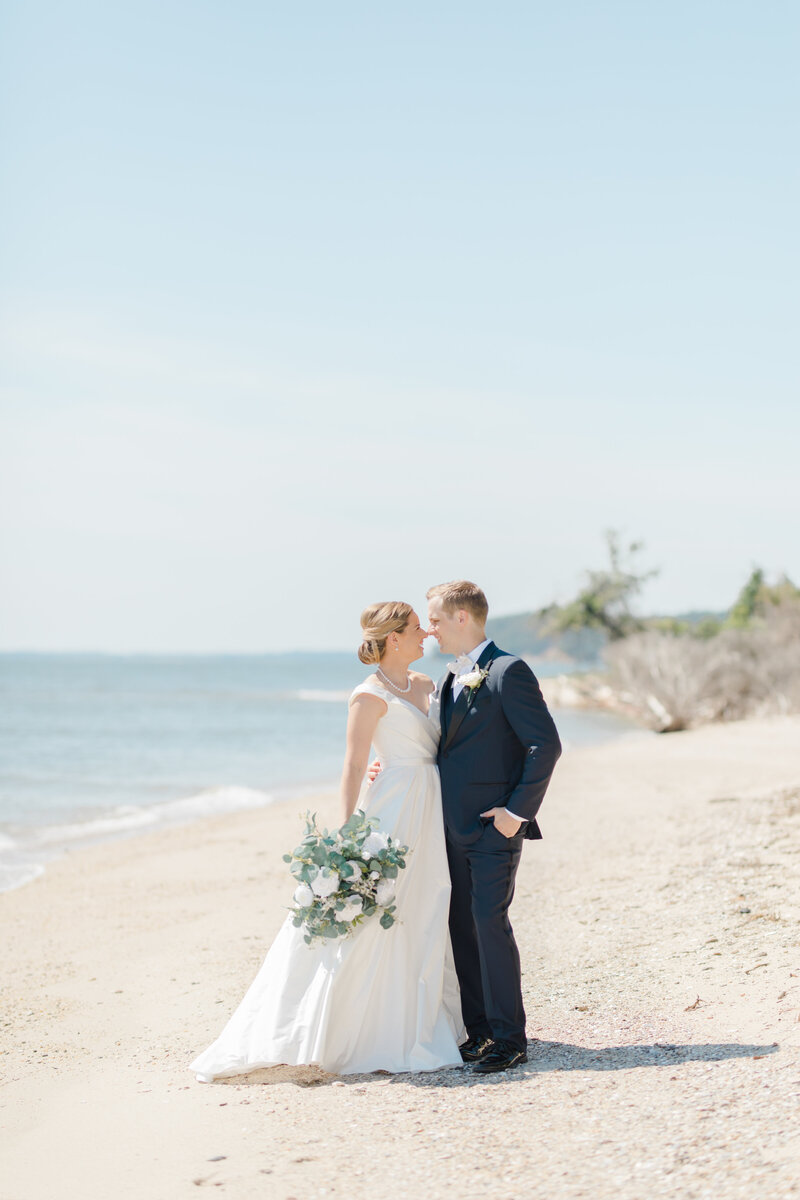 couple kissing on beach at Inn at Perry Cabin wedding in St Michaels Maryland by Costola Photography