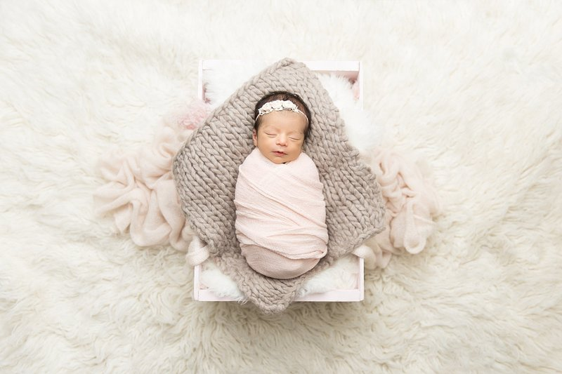 baby girl in light pink wrap