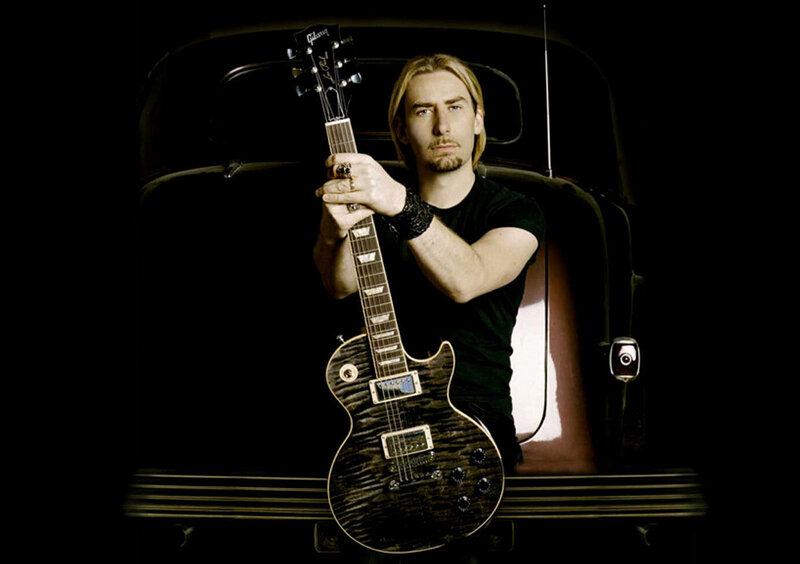 Chad Kroeger portrait sitting on bumper of classic car holding neck of Signature Blackwater Les Paul standing upright in his lap