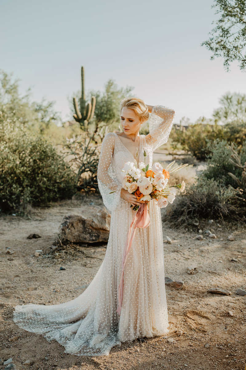 Bride posing with bouquet looking away from camera in Arizona dessert.