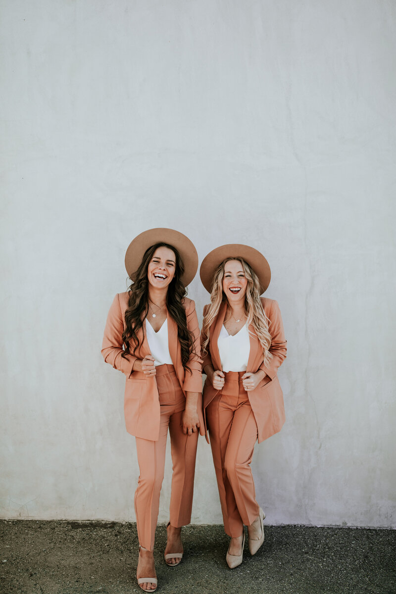 two girls in suits smiling