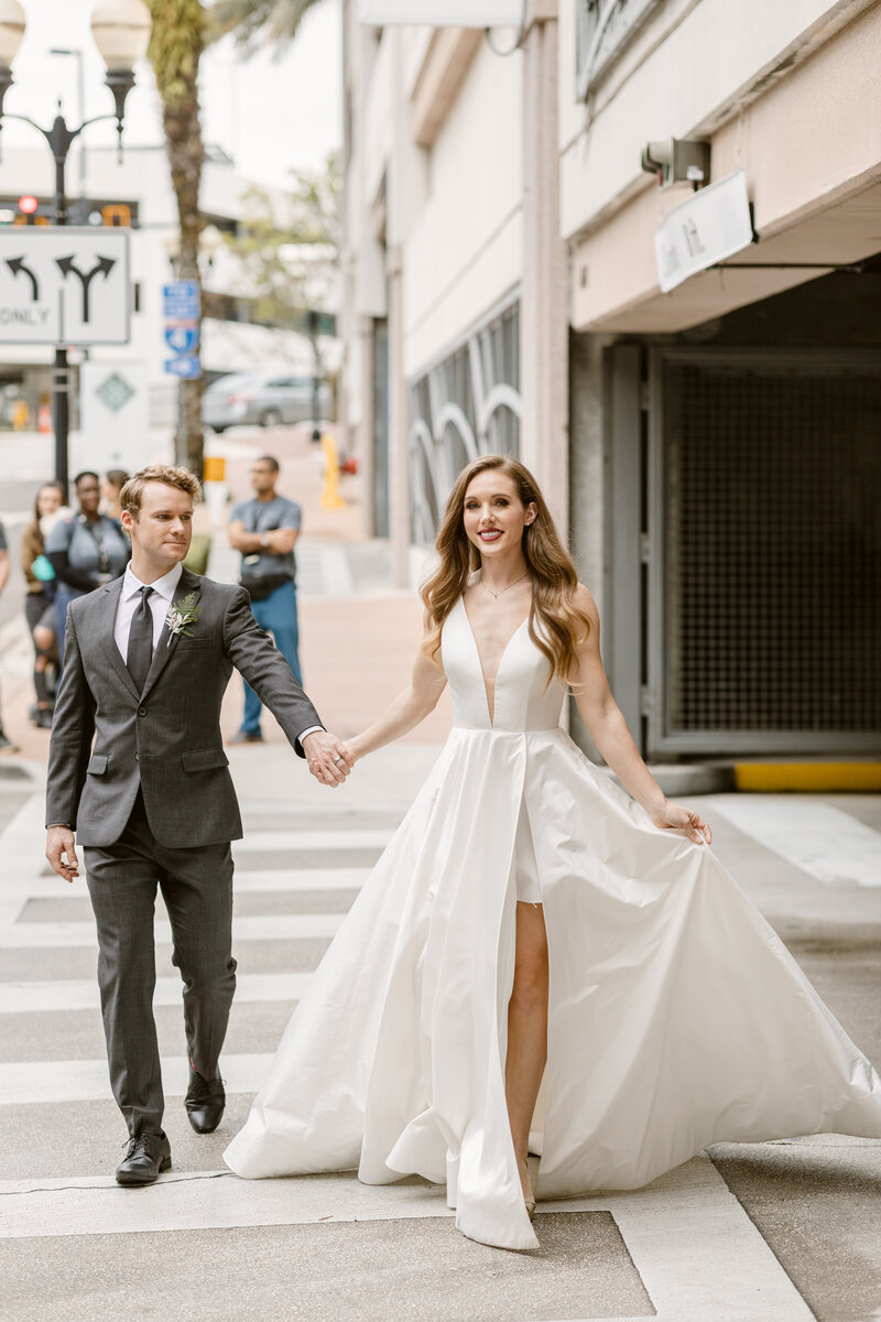 Bride leads her groom through a crosswalk on their wedding day in downtown Orlando