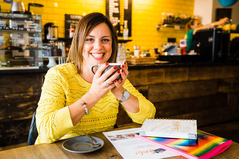 Charlie sits at a table in a cafe holding a cup of coffee.  She is wearing a yellow jumper which matches the yellow tiles int he background.