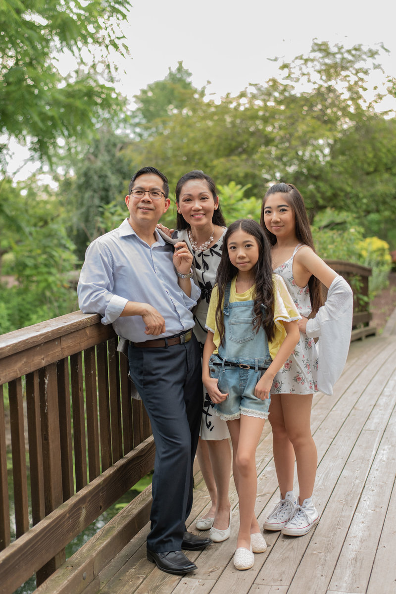 Family of 4 standing together on wooden bridge