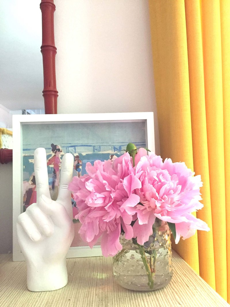 Pink flowers in a vase and  a ceramic peace sign hand on a table.