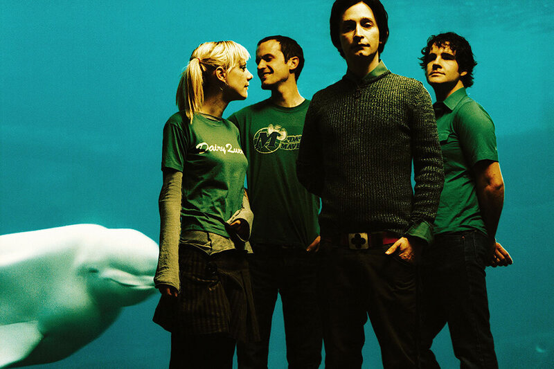 Band portrait Limblifter standing in front of beluga whale aquarium