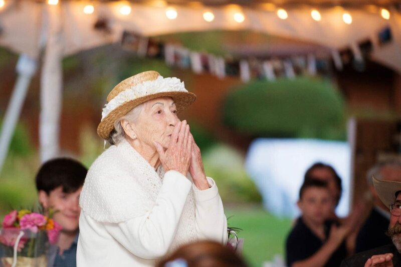 a grandmother kisses her hands to blow air kisses to the couple during the toasts