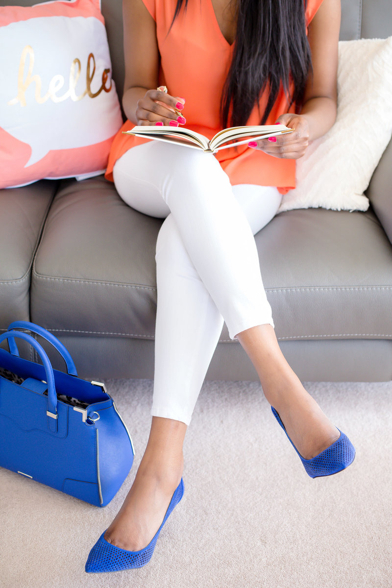 Woman sitting on the couch with blue heels.