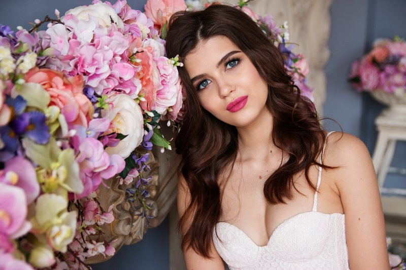 Beautiful brunette bride with pink lipstick poses for photo in wedding dress next to garland of flowers