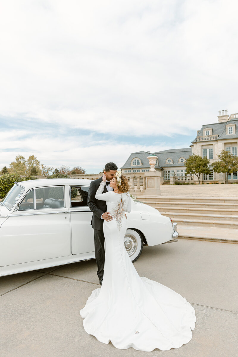 Glamorous bride and groom embrace in front of Rolls Royce on their wedding day