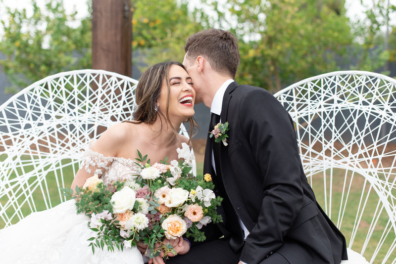 Groom whispers in brides ear who is laughing holding a bouquet at Gather Estate