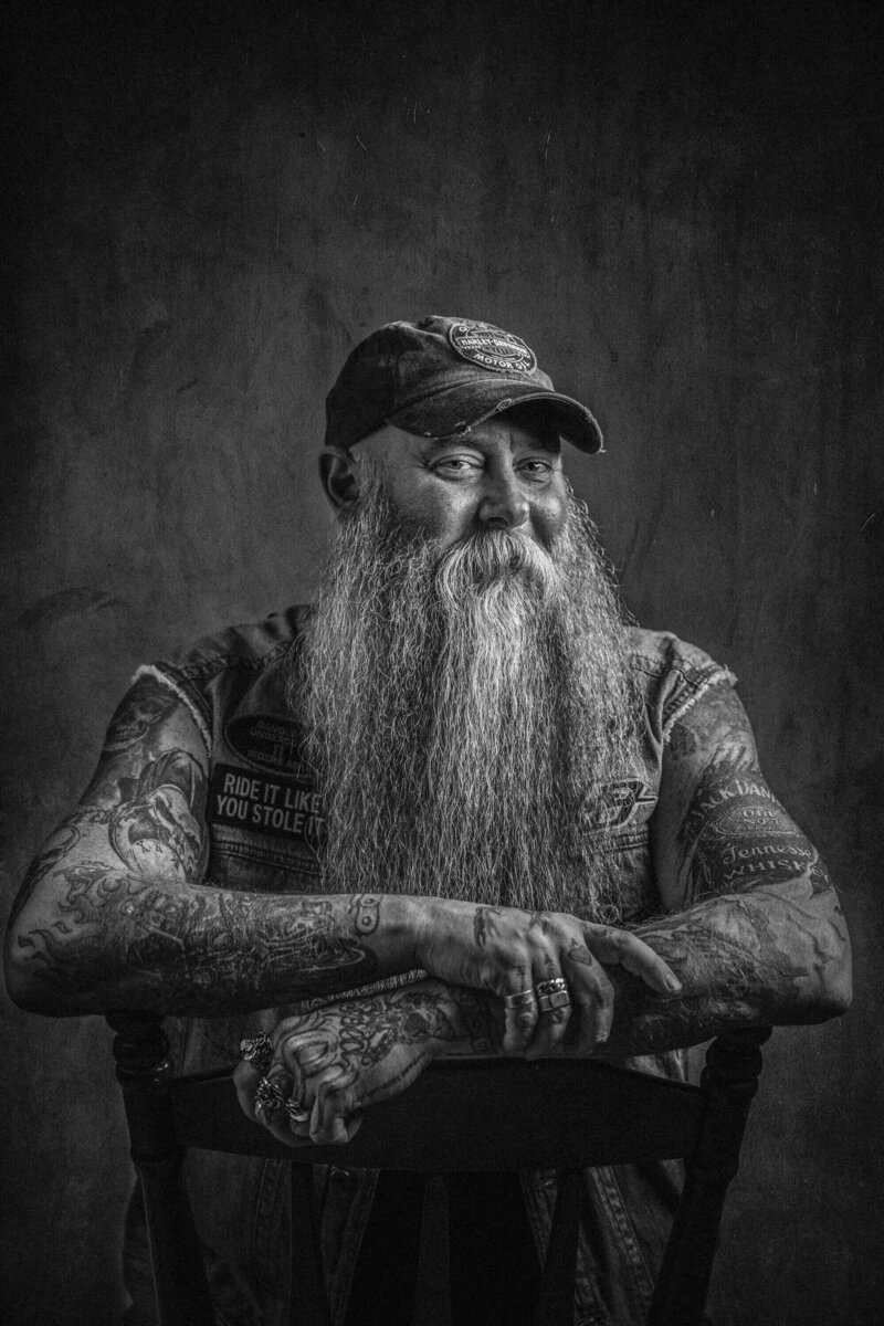 man leans on chair with long beard and tattoos
