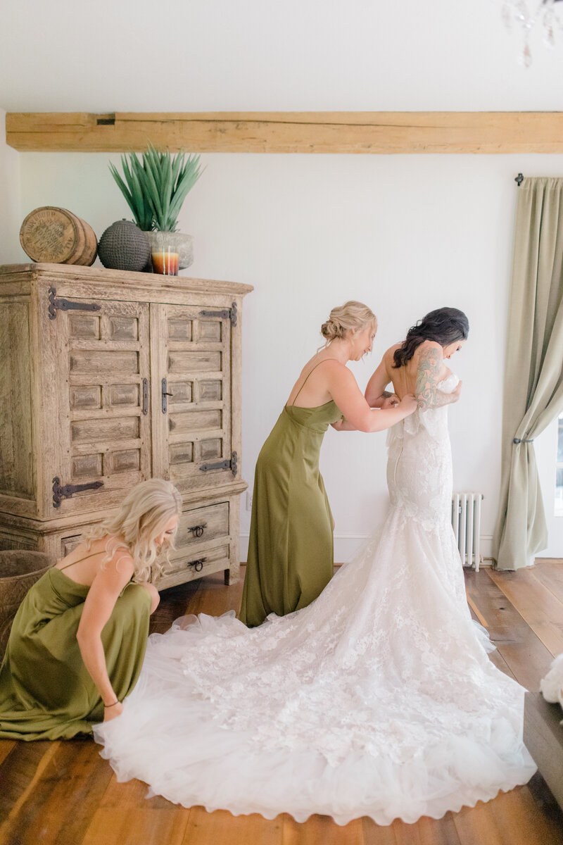 bridesmaids helping bride get dressed in berta at French Inspired Private Estate wedding in charlottesville virginia by costola photography