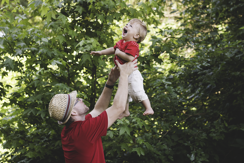 dad tossing son in air for candid laughing photographer ohio