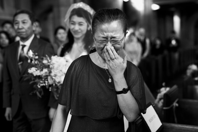 Mother reacting to bride coming down aisle