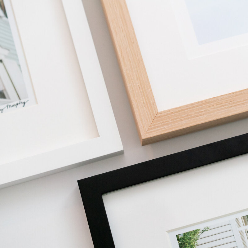 Detail of three photo frames in black, natural wood, and white from Abby Murphy's Charleston photography shop