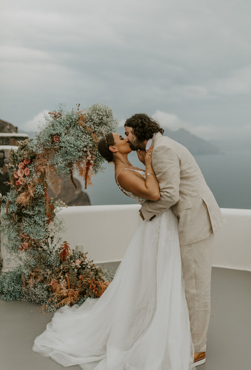 Bride and groom kissing in front of floral arch