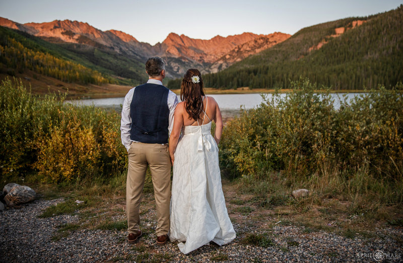 Bride and Groom look out at the lake at Piney River Ranch in Vail