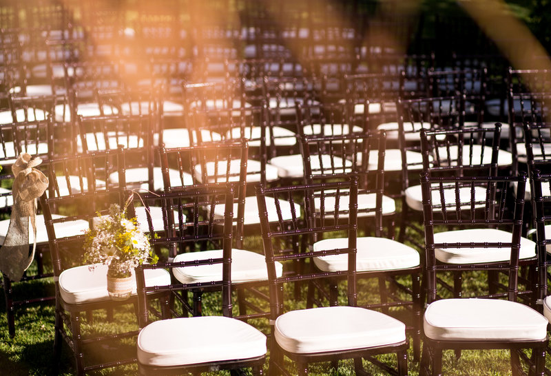 Sun shining, chairs set up outdoors for a wedding ceremony