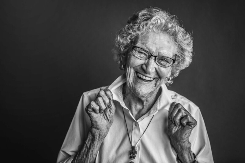 elderly woman laughs and adjusts her collar