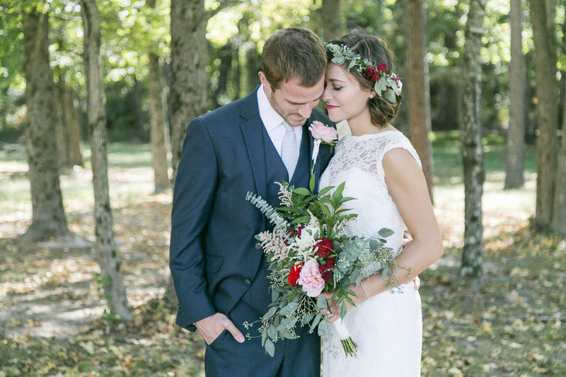 Portrait of a bride and groom standing side by side with a bouquet of flowers in the middle