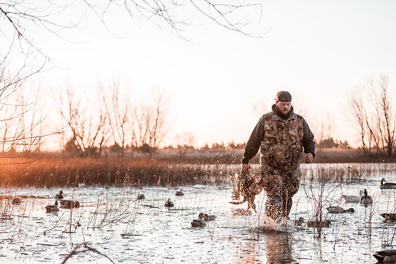 Kansas waterfowl hunter Cody Crook carrying mallards