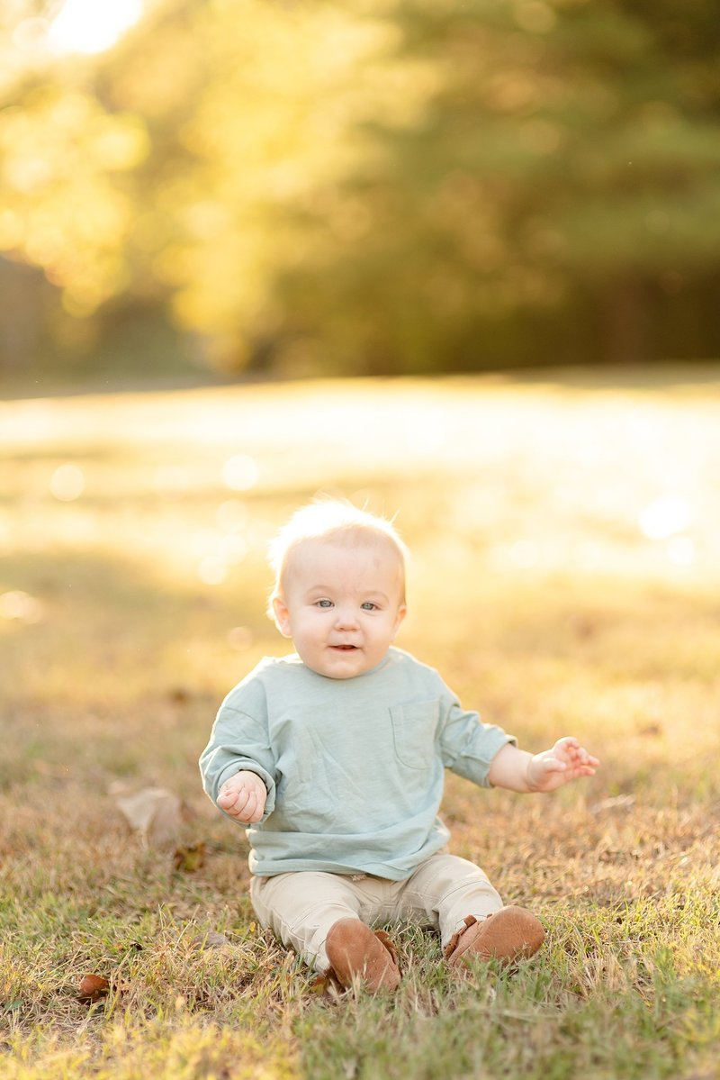 A baby boy is sitting in the grass and is looking at the camera with a soft smile during the golden hour for family portraits in Nashville