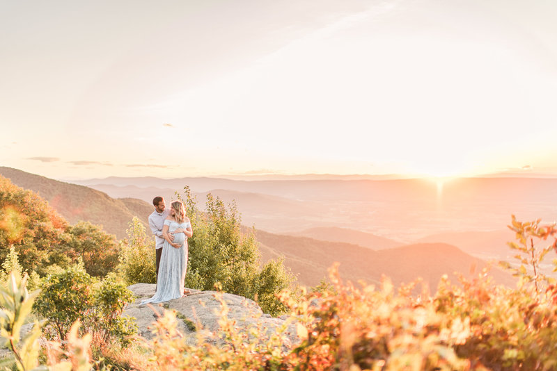 Pregnant couple holding each other on a rock outcrop overlooking the mountains.