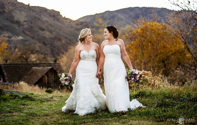 Two beautiful brides walk hand in hand on their fall wedding day at The Golden Hotel in Colorado
