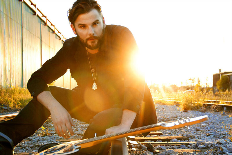 Musician portrait Brad James sitting on gravel between train tracks with guitar sun set burst behind him