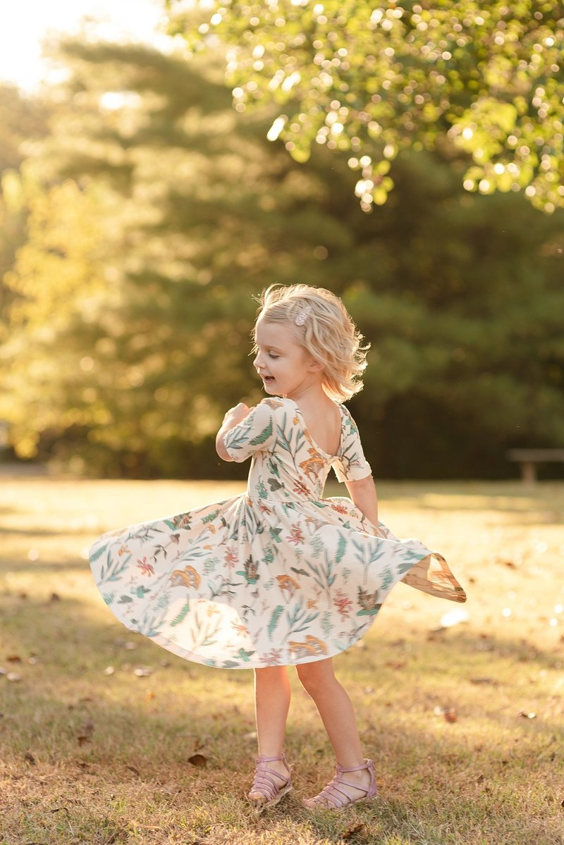 A little girl is twirling in her dress for family portraits in Nashville Tennessee by Dolly DeLong Photography