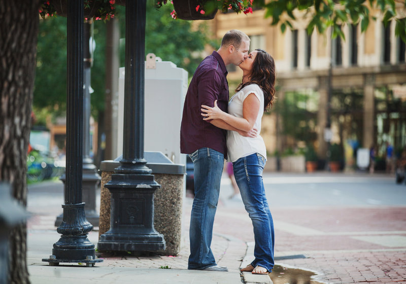 Engaged couple kissing in the streets of downtown St. Paul, Minnesota.