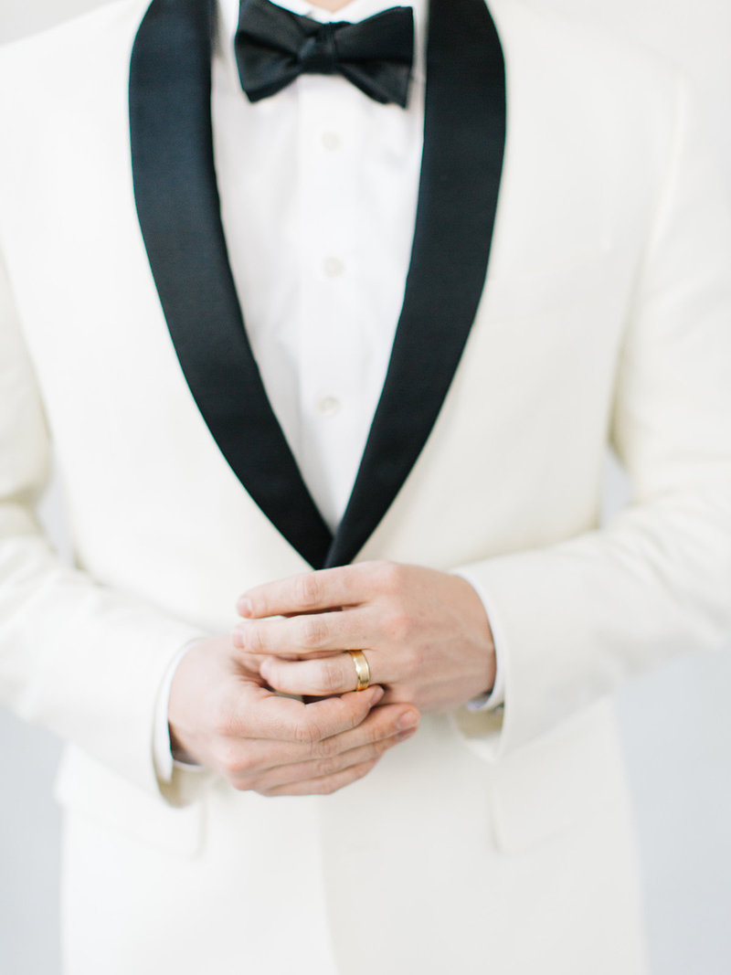 This groom is wearing a classic black and white dinner jacket holding an all white orchid bouquet